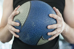 Man holding medicine ball. In heands Stock Photos