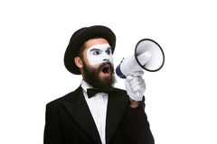 Man holding megaphone make loud noise. Close-up view of man shouting into a megaphone, isolated on white background Royalty Free Stock Photo