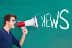 Man Holding Megaphone with News Announcement. Young Man Holding Megaphone with News Announcement On Blackboard Stock Photo