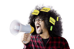 Man holding megaphone with sticky notes. Afro man shouting by using megaphone with help word on sticky notes,  on white background Stock Photos