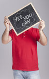 Man holding message written on a blackboard. Man holding Yes You Can message written on a blackboard Royalty Free Stock Photography