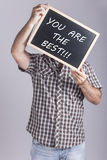 Man holding message written on a blackboard. Man holding You Are The Best message written on a blackboard Stock Images