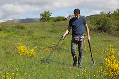 Man holding metal detector. A man searching for buried treasure, ancient coins and historic artefacts with metal detector stock image