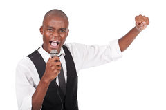 Man holding a microphone and singing. Young and beautiful black man holding a microphone and singing Royalty Free Stock Photos