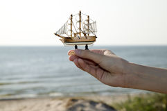 Man is holding miniature ship Stock Photography