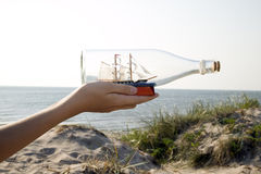 Man is holding miniature ship in bottle Royalty Free Stock Image