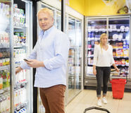 Man Holding Mobile Phone While Choosing Juices In Grocery Store Stock Photo
