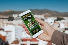 Sports betting app in a mobile phone screen. Man holding a mobile phone in the hand with sports betting website in the screen royalty free stock photography