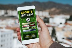 Sports betting app in a mobile phone screen. Man holding a mobile phone in the hand with sports betting website in the screen, with city background royalty free stock photography