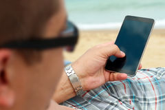Man holding a mobile phone. internet connection on the beach. Sea behind Stock Photos