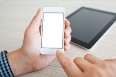 Man holding a mobile phone with isolated screen above the table Stock Photography