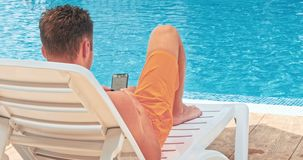 Man while relaxing by the pool stock footage