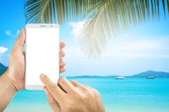 Man holding mobile phone  screens display on the b. Man hands holding mobile phone  screens display on the beach background Royalty Free Stock Photo