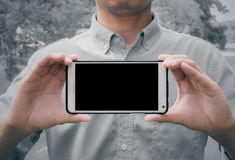 Man holding mobile smart phone. Black LCD with clipping path for the screen (vintage style color Royalty Free Stock Photography
