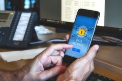 Man holding a mobile smart phone with a data security application displaying a yellow padlock stock images