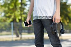 Mysterious guy with smartphone and headphones in hands on the park. stock photos