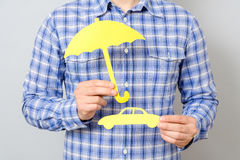 Man holding model of car and yellow umbrella. Concept for car insurance Stock Photography
