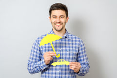 Man holding model of car and yellow umbrella. Concept for car insurance Stock Images