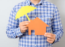 Man holding model of house. Concept for home insurance. Man holding model of house covered yellow umbrella. Concept for home insurance Stock Photography