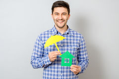Man holding model of house. Concept for home insurance. Man holding model of house covered yellow umbrella. Concept for home insurance Stock Images