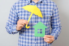 Man holding model of house. Concept for home insurance. Man holding model of house covered yellow umbrella. Concept for home insurance Stock Photo