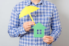 Man holding model of house. Concept for home insurance. Man holding model of house covered yellow umbrella. Concept for home insurance Royalty Free Stock Photo
