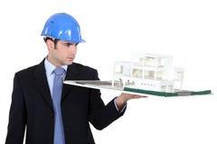 Man holding model housing Stock Image