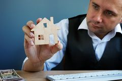 Free Man Holding Model Of Home. Property Investment And House Mortgage Stock Photo - 131649140
