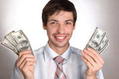 Man Holding Money. The businessman in a white shirt. The man shows money. Dollars are developed by a fan Royalty Free Stock Images