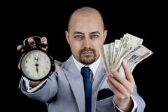 Man holding Money and alarm wearing a business suit, race against the clock, deadline Royalty Free Stock Photography