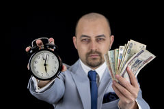 Man holding money and alarm wearing a business suit, race against the clock, deadline Stock Photo
