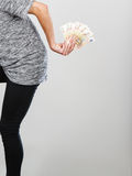 Man holding money behind his back. Rich, finances, miser concept. Man holding money behind his back, studio shot on grey background stock photos