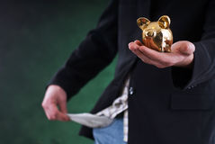 Man holding money box. In one hand and with the other showing empty pocket, isolated on black Stock Photography