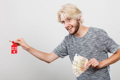 Man holding money and keys to house. Household savings and finances, economy concept. Happy man holding money and keys to house, studio shot on grey background stock image