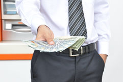 A man holding money US dollar bills in front of ATM background Royalty Free Stock Images
