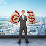 Man holding moneybags with dollar and euro signs Royalty Free Stock Image
