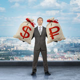 Man holding moneybags with dollar and ruble signs Stock Image