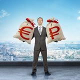 Man holding moneybags with euro and ruble signs Stock Images