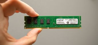 Man holding new RAM by Micron by Crucial. LONDON, UK - DEC 29, 2018: Man holding in hand new powerful RAM manufactured by Crucial by Micron for powerful servers royalty free stock image