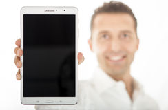 Man holding new Samsung Galaxy Tab Pro 8.4 16GB. A smiling man holds the new Samsung Galaxy Tab Pro 8.4 16GB (Wi-Fi) Touchscreen Android White - Focus on the stock photos