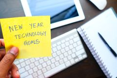 Man holding New year technology goal written on colored sticker notes against technology background. Man holding New year technology goal written on colored Stock Images