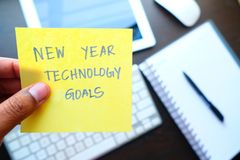 Man holding New year technology goal written on colored sticker notes against technology background. Man holding New year technology goal written on colored Stock Photos