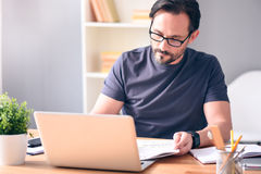 Man holding newspaper in front of laptop Royalty Free Stock Photography