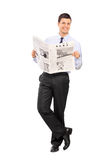 Man holding newspaper and leaning on a wall Stock Image
