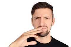 Man holding nose against bad smell. Portrait of young man holding his nose against a bad smell. Isolated white background Royalty Free Stock Photos