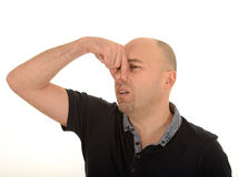 Man holding nose due bad smell. Side portrait of middle aged man holding nose due to bad smell, white background stock photo