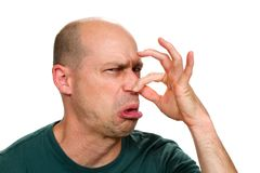 Man Holding Nose. Man smells something stinky and pinches his nose to stop the bad odor stock photography
