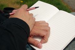 Man Holding Note Book. A mans hands resting on an open notebook on his lap while holding a pen Royalty Free Stock Photos