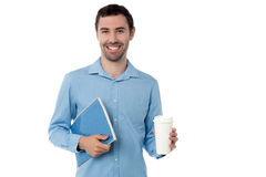 Man holding notebook and beverage Stock Photo