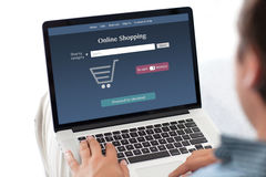 Man holding notebook with online shopping on the screen Stock Images